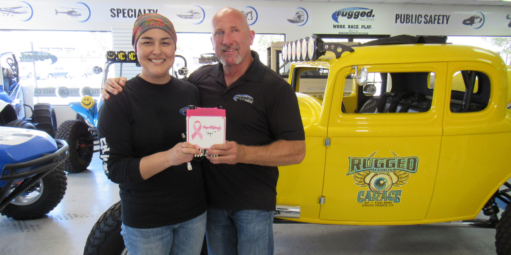 Taryn Timothy and Greg Cottrell of Rugged Radios pose with one of the special edition pink radios they sold to raise funds for cancer treatment.